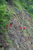 Red climbers. Climbers solving rock problems fallen on the road of Olt valley in Romania due to big raining Royalty Free Stock Photography