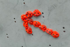 Red climbing holds in the shape of an arrow on grey wall Stock Photography