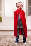 Red cloak  kid livingroom superhero Stock Photo