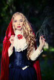 Red cloak. Portrait of a stunning blonde lady in old-fashioned dress and red cloak in a fairy forest royalty free stock photography