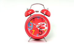 Red clock. Small red alarm clock  on white background Royalty Free Stock Photo