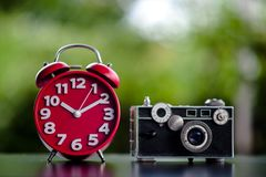 Red clock and camera Put on the table Time and shooting equipment Concepts of punctuality and photography stock photography