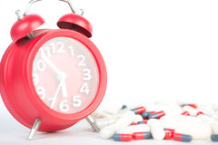 Red clock and capsule show healthcare and medicine time concept Stock Images