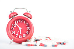 Red clock and capsule show healthcare and medicine time concept Royalty Free Stock Photos