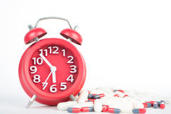 Red clock and capsule show healthcare and medicine time concept Stock Photos
