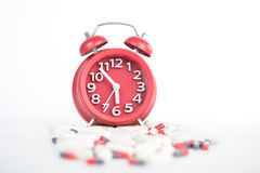 Red clock and capsule show healthcare and medicine time concept Royalty Free Stock Photography