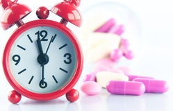 Red clock and medicine background. Show medicine concept Stock Images