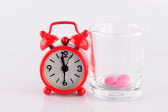 Red clock and medicine glass on. White background show medicine time concept Stock Photos