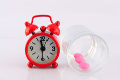 Red clock and pink tablet in dosage glass on white background. Show medicine time concept Stock Photos