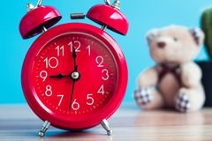 Red clock placed on wooden table on blue background.  Royalty Free Stock Photography