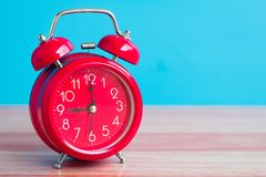 Red clock placed on wooden table on blue background.  Stock Images