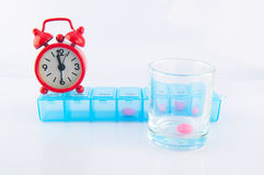 Red clock and prescription pill box. Show medicine time concept Stock Image