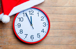 Red clock and santa claus hat on the wonderful brown wooden back Royalty Free Stock Photo