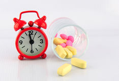 Red clock and tablet in glass on white background. Show medicine time Stock Photography