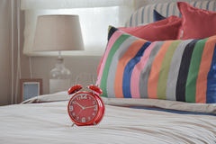 Red clock on white blanket and colorful striped pillows Royalty Free Stock Photos