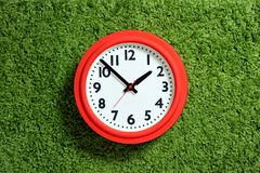Red clock with white dial on the green carpet Stock Photo