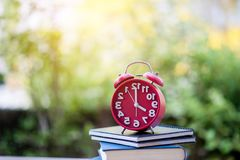 Teaching Ideas Punctuality And focus on time. Red Clocks and Books Teaching Ideas Punctuality And focus on time royalty free stock image