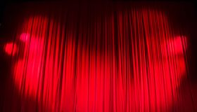 Red closed curtain with light spots in a theater Stock Images