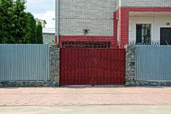 Red closed gates and an iron fence in front of the facade of a private house. Gray metal fence with closed gates in the street in front of a brick house with Stock Photos