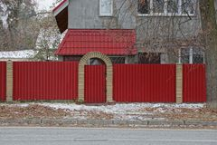 Red closed metal gates and part of the fence at the asphalt road. Private red closed metal gates and part of the fence on the asphalt road stock image