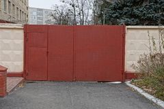 Red closed metal gates and part of the fence at the asphalt road. Private red closed metal gates and part of the fence on the asphalt road royalty free stock photos