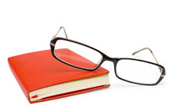 Red closed notepad  and glasses isolated on white Stock Images