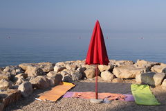 Red closed parasol on the beach Stock Image