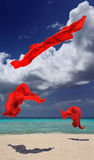 Red cloth dancing. 3 pieces of red cloth in mid air on a white sand beach with the sea in the background Royalty Free Stock Photos