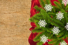 Red cloth with fir tree branch over wooden texture Stock Photos