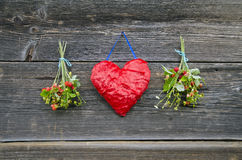 Red cloth heart and two bunch wild strawberry on wall Royalty Free Stock Images