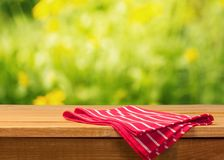 Red cloth napkin on wooden table. Red cloth napkin table green background design Stock Image