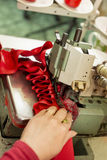 Red Cloth Ruffled Through Sewing Machine Stock Photography