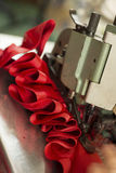 Red Cloth Stitched and Ruffled Through a Sewing Machine Stock Photo