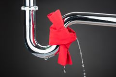Red Cloth Tied On Leakage Pipe. Over The Gray Background Royalty Free Stock Image