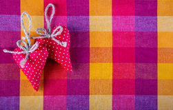 Red cloth two handmade hearts on checkered cloth napkin. Stock Photo