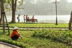 Red cloth woman gardener wearing Vietnamese conical hat cut grass in yard of outdoor park near  Hoan Kiem Lake in Hanoi, Vietnam.  Stock Photos