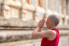 Red clothes young monk salute respect in a park of buddhist temple Royalty Free Stock Photography