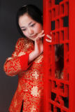 A red clothing girl of China. A Chinese girl in traditional dress ponders in front of the ancient window Stock Image