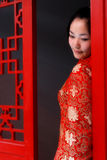 A red clothing girl of China. A Chinese girl in traditional dress ponders in front of the ancient window Royalty Free Stock Photos