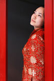 A red clothing girl of China. A Chinese girl in traditional dress is in front of the ancient gate Royalty Free Stock Photo