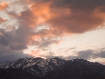 Red clouds sunset over snowy mountains. In Persian desert Royalty Free Stock Photography