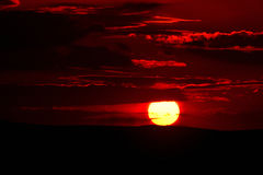 Red Cloudy Sunset. Zoomed in sunset with red clouds above hillside Royalty Free Stock Photography