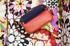 Red clutch bag on milticolor flowers. Clutch bag  on multicolor background Royalty Free Stock Image