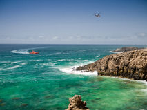 Red coastguard boat and rescue helicopter. Red coastguard boat and white rescue helicopter above green ocean water and rocky shore Royalty Free Stock Images