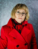Red coat. Mature blond woman in red coat Royalty Free Stock Images