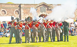 Red coat soldiers firing rifles at Fort George. 'The celebration of the Centuries' ; Red coat soldiers firing their rifles while taking part in the re-enactment Stock Images