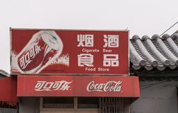 Red Coca-Cola sign with spelling error in Beijing, China. Beijing, China - April 26, 2010: Closeup of red Coca-Cola sign fixed on gray roof against silver sky Royalty Free Stock Photos