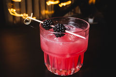 Red  cocktail with berries on top Royalty Free Stock Images