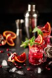 Red cocktail with blood orange and pomegranate. Refreshing summer drink on dark background stock photo