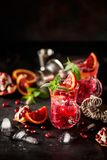 Red cocktail with blood orange and pomegranate. Refreshing summer drink on dark background royalty free stock photography
